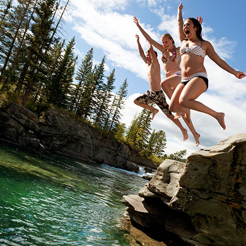Teenagers jumping into a river at Castle Falls