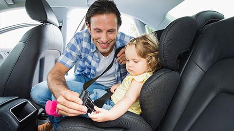 Niño en asiento de vehículo junto con su padre