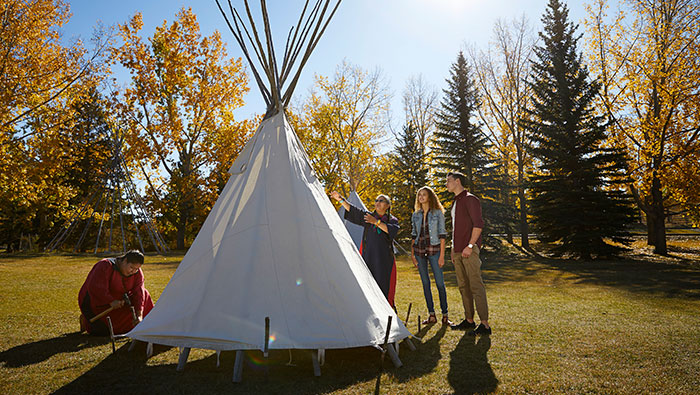 Visitors learning how to set up a tipi