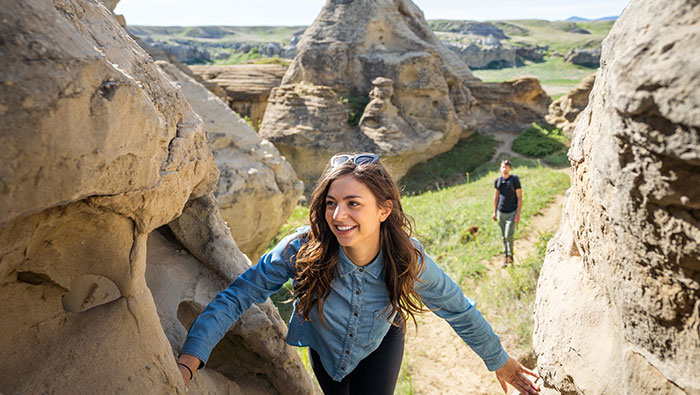 woman hiking between 2 rocks at writing on stone provincial park